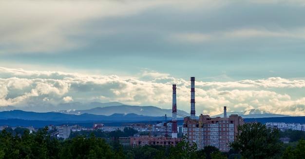 Ampio panorama del moderno cantiere urbano del quartiere degli appartamenti residenziali in città con alberi verdi, gru a torre funzionanti, camini a tubo alto sotto il cielo blu sulla catena montuosa distante