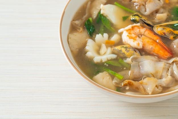 Spaghetti di riso larghi con frutti di mare in salsa di sugo - stile di cibo asiatico