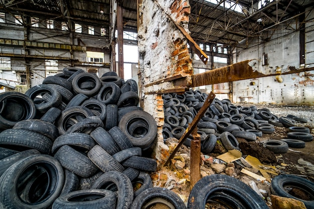 Ampia ruota di gomma dell'auto che giace sullo sfondo di pneumatici usati con perdite di luce in un vecchio impianto. pneumatici consumati a terra in una fabbrica abbandonata in rovina al chiuso