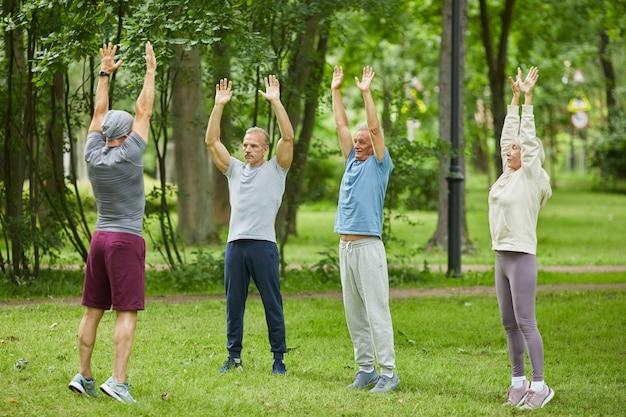 Grandangolo di persone anziane attive che fanno le mani in alto esercizio di stretching davanti al loro allenatore nel parco cittadino