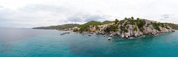Campo lungo della costa del mar egeo della grecia, edifici loutra situati vicino alle scogliere rocciose, vegetazione e acqua blu. vista dal drone