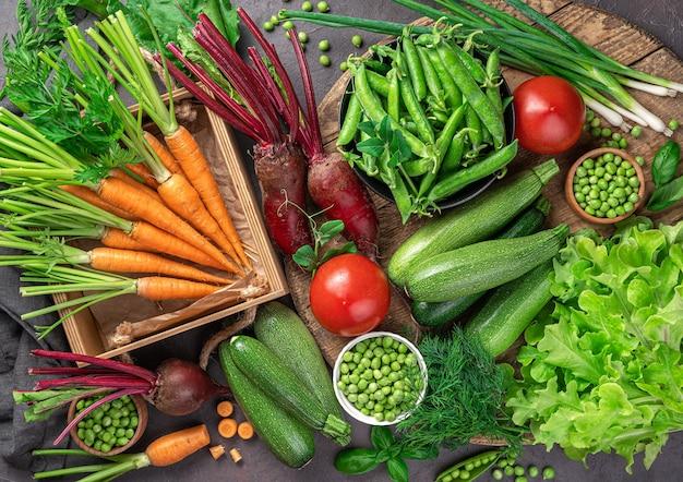 Un'ampia varietà di verdure giovani e fresche su uno sfondo marrone. prodotti sani e rispettosi dell'ambiente.