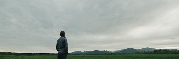 Immagine ampia vista del giovane in abbigliamento casual in piedi nella splendida natura sotto il cielo nuvoloso grigio guardando in lontananza.