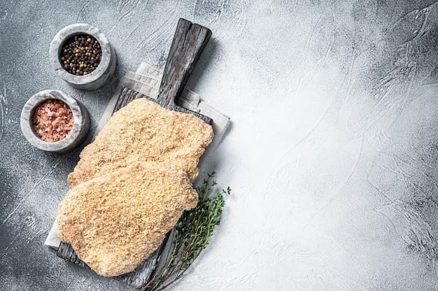 Wiener cotoletta cruda nel pangrattato su tavola di legno. sfondo bianco. vista dall'alto. copia spazio.