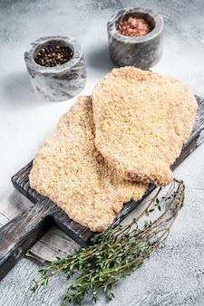 Wiener cotoletta cruda nel pangrattato su tavola di legno. sfondo bianco. vista dall'alto.