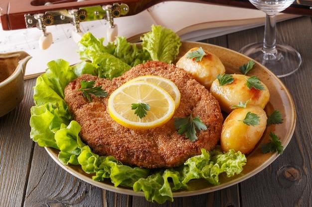 Cotoletta alla milanese con patate e insalata, messa a fuoco selettiva.