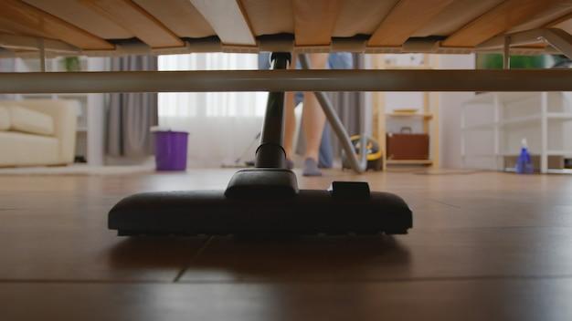 Moglie che pulisce la polvere sotto il divano con l'aspirapolvere
