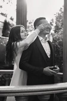 La moglie chiude gli occhi dello sposo in piedi dietro