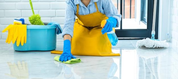 Concetto di pulizia e pulizia della moglie, giovane donna felice in guanti di gomma blu che pulisce la polvere usando uno spray e uno spolverino mentre si pulisce sul pavimento a casa