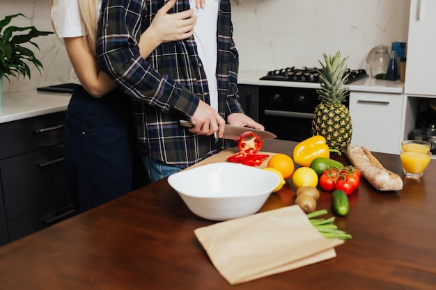 Moglie che abbraccia il marito mentre fa insalata con verdure fresche in cucina