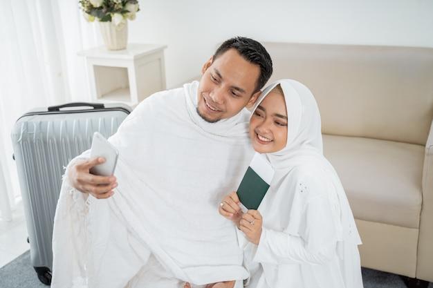 Moglie e marito in abiti tradizionali bianchi selfie