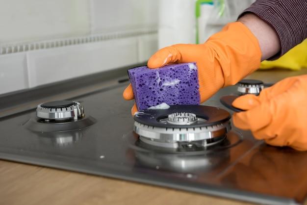 La moglie in cucina si asciuga con guanti gialli, pulisce per prendersi cura e proteggersi. lavori domestici di igiene