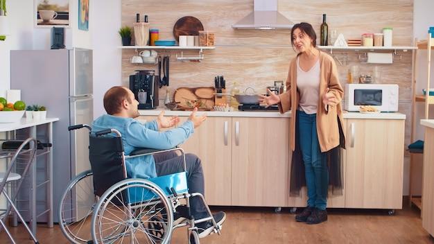 Moglie che urla in cucina al suo uomo disabile in sedia a rotelle mentre è in disaccordo. ragazzo con paralisi handicap disabilità handicappato difficoltà a ottenere aiuto per la mobilità dall'amore e dalla relazione
