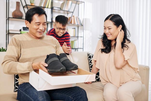 Moglie e figlio che guardano felice eccitato uomo di mezza età che apre la scatola di cartone con le scarpe da corsa che voleva così tanto