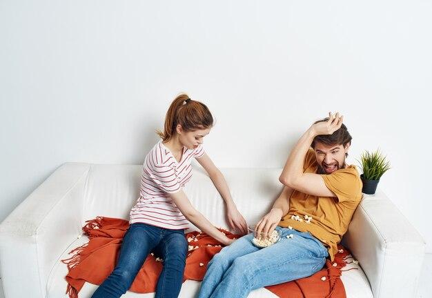 Moglie con marito a casa sul divano a guardare film in famiglia