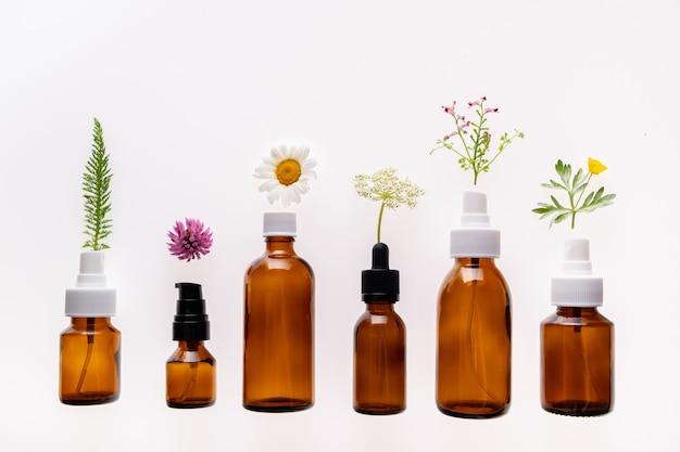 Fiori selvaggi e bottiglia di vetro della medicina su bianco