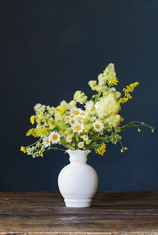 Fiori selvatici in vaso bianco su oscurità Foto Premium