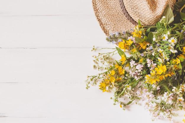 Fiori selvaggi con cappello di paglia su bianco
