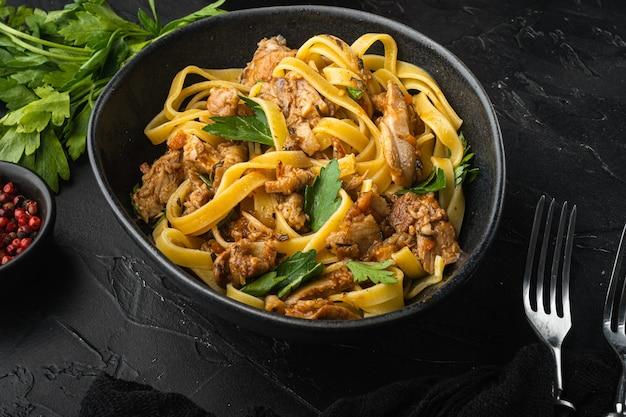 Lepre selvatica con verdure in salsa di vino bianco tagliatelle di pasta o pappardelle set, nella ciotola, sul tavolo di pietra nera