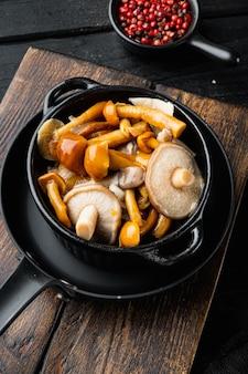 Funghi porcini boletus edulis e boletus tappo in un barattolo impostato, sul tavolo in legno nero tabella