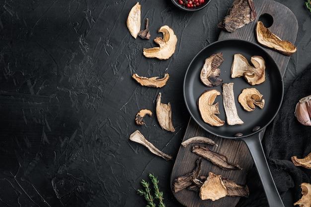 Set di funghi porcini secchi biologici selvatici in padella in ghisa, su fondo nero