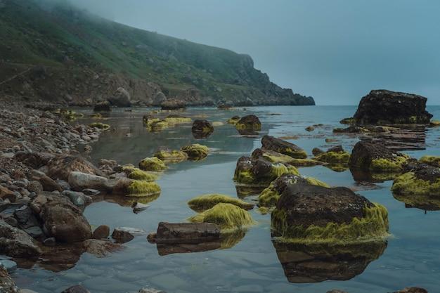 Mare selvaggio durante l'inverno. scenario drammatico con nuvole scure e nebbia pesante sopra l'acqua.