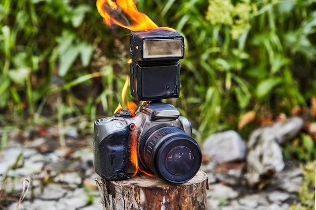 Wildfire ha distrutto la telecamera dei turisti. i turisti hanno dimenticato una macchina fotografica su un ceppo. il fuoco ha distrutto la telecamera. il gadget è stato bruciato, fuso e guasto, è difettoso e non adatto alla fotografia.