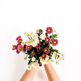 Mazzo di fiori di campo nelle mani della ragazza sulla superficie bianca