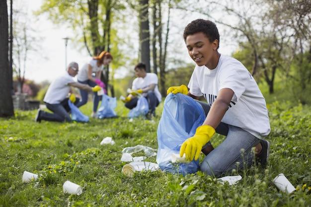 Volontario della fauna selvatica. volontario maschio energico che usa il sacco della spazzatura mentre raccoglie i rifiuti