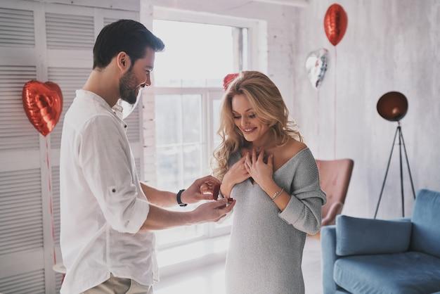 Vuoi sposarmi? giovane donna sorpresa che guarda l'anello di fidanzamento con un sorriso mentre si trova in camera da letto piena di palloncini balloon