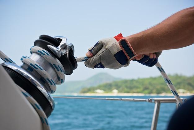 Verricello e marinai mani su una barca a vela. scatto con messa a fuoco selettiva