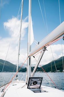 Verricello della barca a vela bianca con un portello di vetro aperto della corda rossa a prua della nave