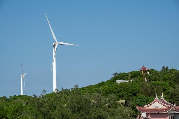 La turbina eolica in funzione sulla montagna è sotto il cielo azzurro