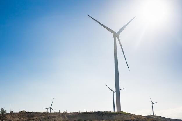 Turbine eoliche che generano elettricità con cielo blu - concetto di risparmio energetico.