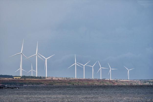 Ruote del vento in mare su cielo blu. energia eolica.