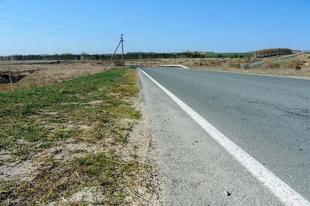 Un'autostrada tortuosa che si estende in lontananza sullo sfondo di un bellissimo paesaggio primaverile, campi, prati, boschi e colline. strisce stradali su asfalto. la prospettiva di un viaggio on the road.