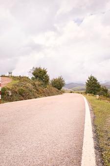 Strada tortuosa della montagna fra i campi verdi sotto le nuvole di autunno