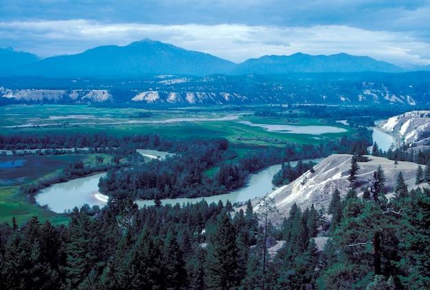 Fiume di bobina che attraversa valle remota con montagne sullo sfondo