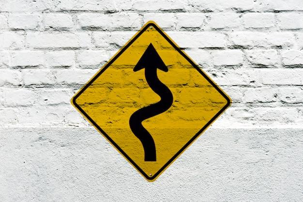 Strada tortuosa avanti a sinistra: cartello stradale stampato sul muro bianco, come un graffito