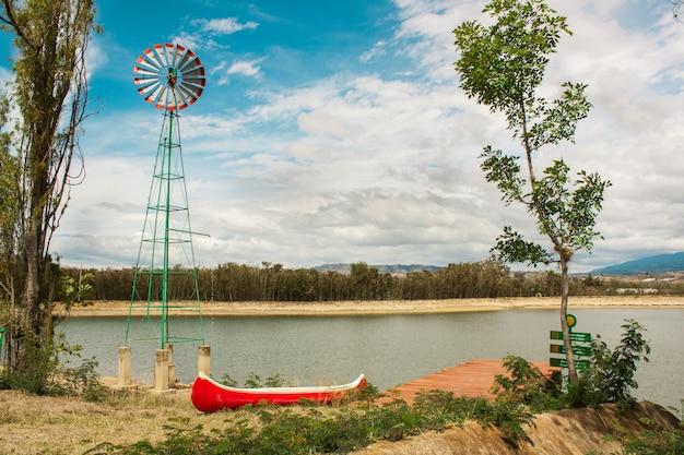 Mulino a vento con una barca su un lago