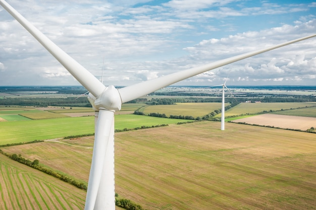 I mulini a vento generano elettricità nei campi. fonti alternative di energia, primo piano delle turbine eoliche da un'altezza. bella vista dal drone