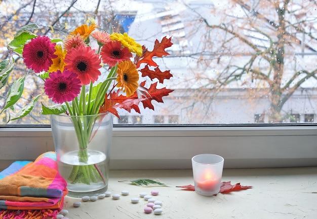Bordo della finestra con un mazzo di fiori di gerbera in vaso di vetro. alberi autunnali o invernali dietro la finestra.