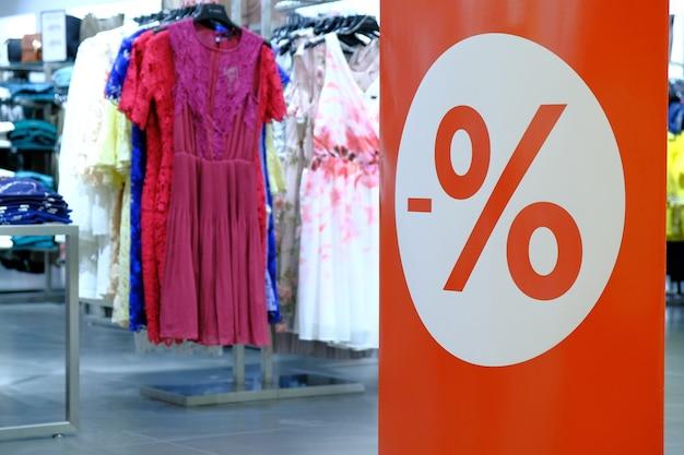 Finestra della boutique con segni di pubblicità in vendita per abiti femminili presso il centro commerciale.