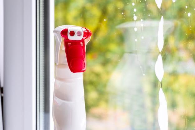 Detergente per vetri in plastica detergente per bottiglie con tappo rosso. pulizie di primavera, concetto di lavoro domestico