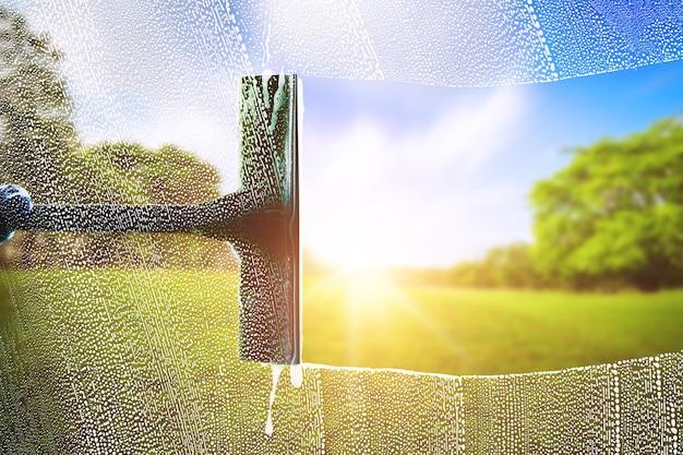 Detergente per vetri per il lavaggio di finestre su un parco verde