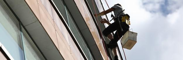 Pulizia delle finestre da parte di uno scalatore su un edificio alto