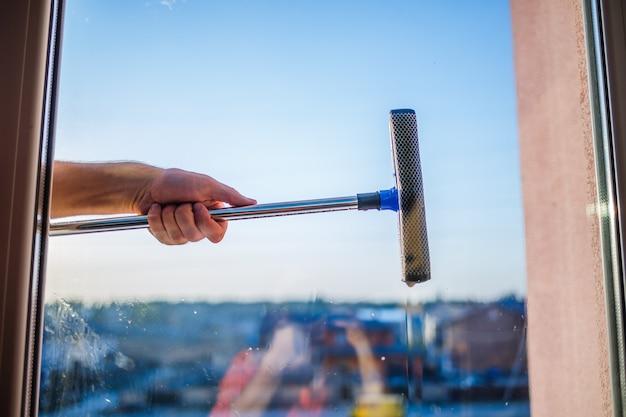 Pulizia delle finestre in grattacieli, case con una spazzola. spazzola per la pulizia dei vetri. ampia vetrina in edificio multipiano, servizio di pulizia. rimozione polvere e lavaggio vetri.