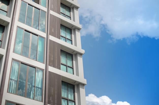 Griglia della finestra della costruzione moderna del condominio con il fondo bianco del cielo blu della nuvola