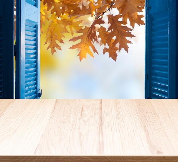 Sfondo del davanzale della finestra con paesaggio autunnale e spazio libero per la decorazione, foglie autunnali e tavolo in legno