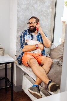 Davanzale della finestra. sorridente uomo d'affari dai capelli scuri sentirsi rilassato mentre è seduto sul davanzale della finestra accogliente con cuscini